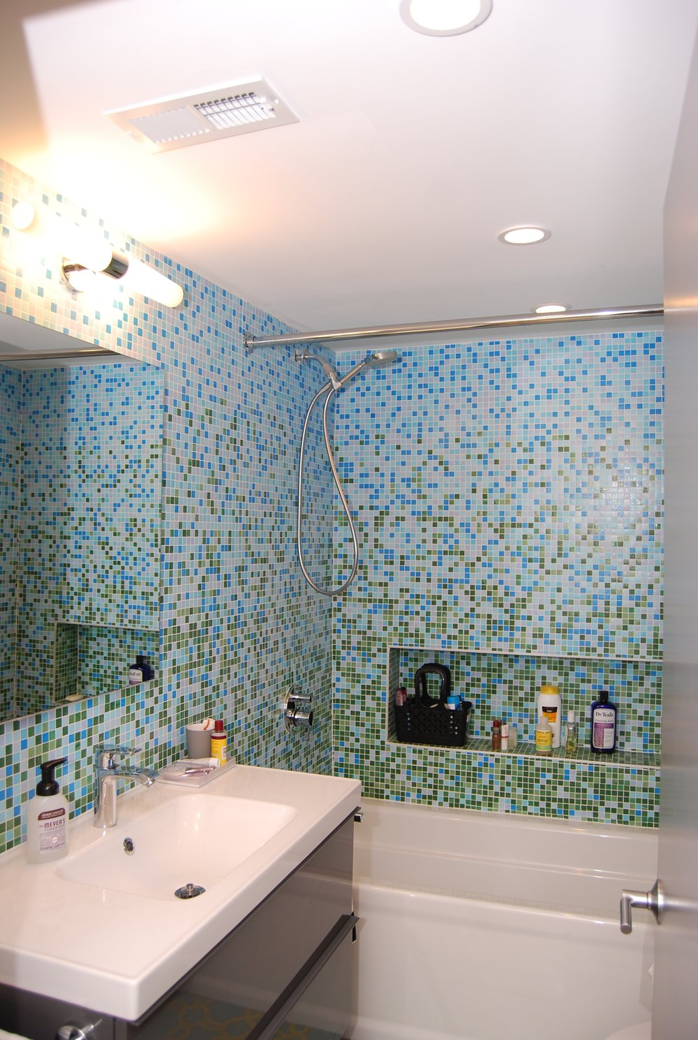 The finished hall bathroom. Some additional wall space was found during demo and we inserted a long soap/shampoo niche.