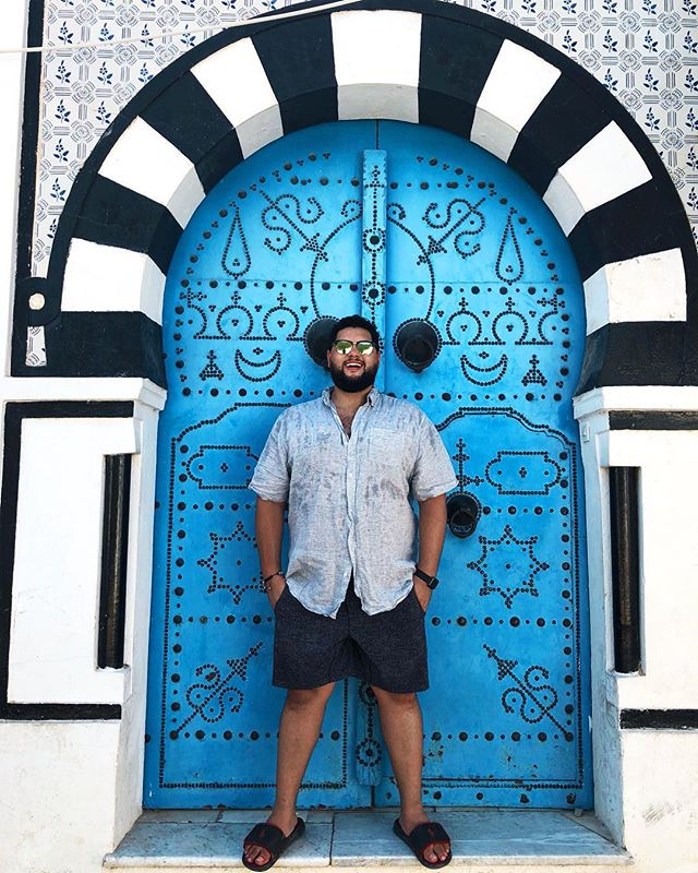 This is a picture of me smiling in front of a blue door in Africa 😁 • • • • • #vlogger #djlife #djlifestyle #djtour #tourlife #vlogsquad #vlogging #travelvlog