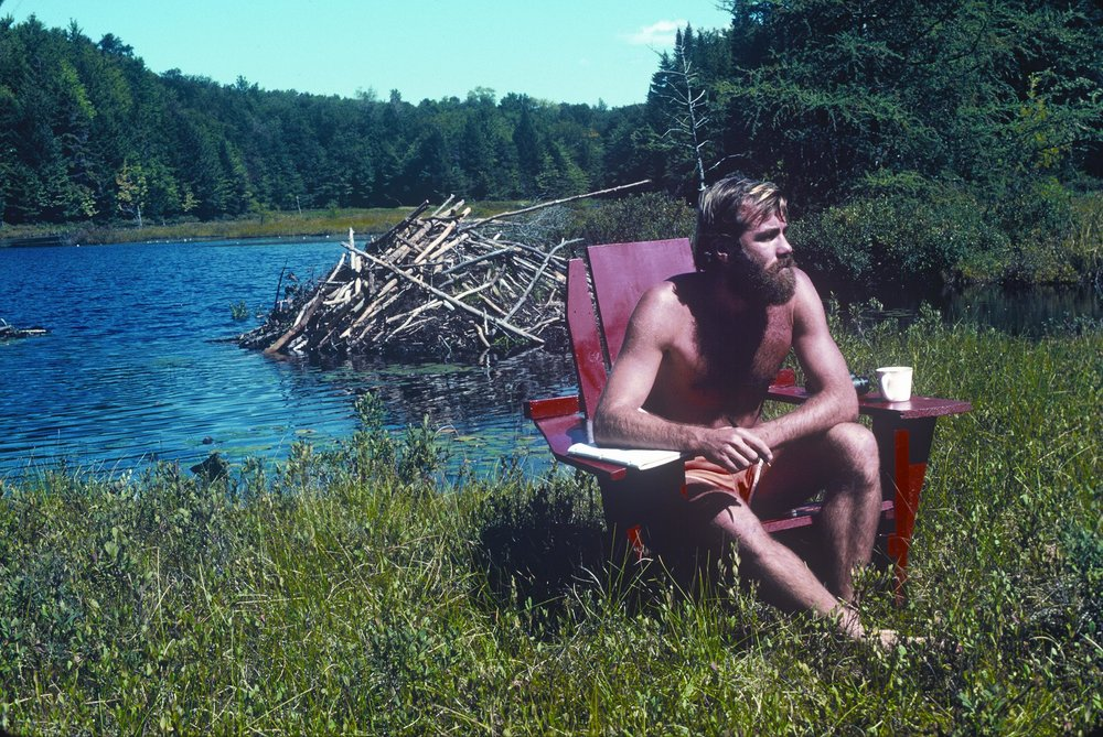 John Slade, aged 33, 1980, in northern New York State. This was my office, away from family on a lake in the Adirondack Park. I am sitting in a chair which my grandfather built, on a floating bog, in a small lake in a huge forest. In the background is a thriving beaver lodge.