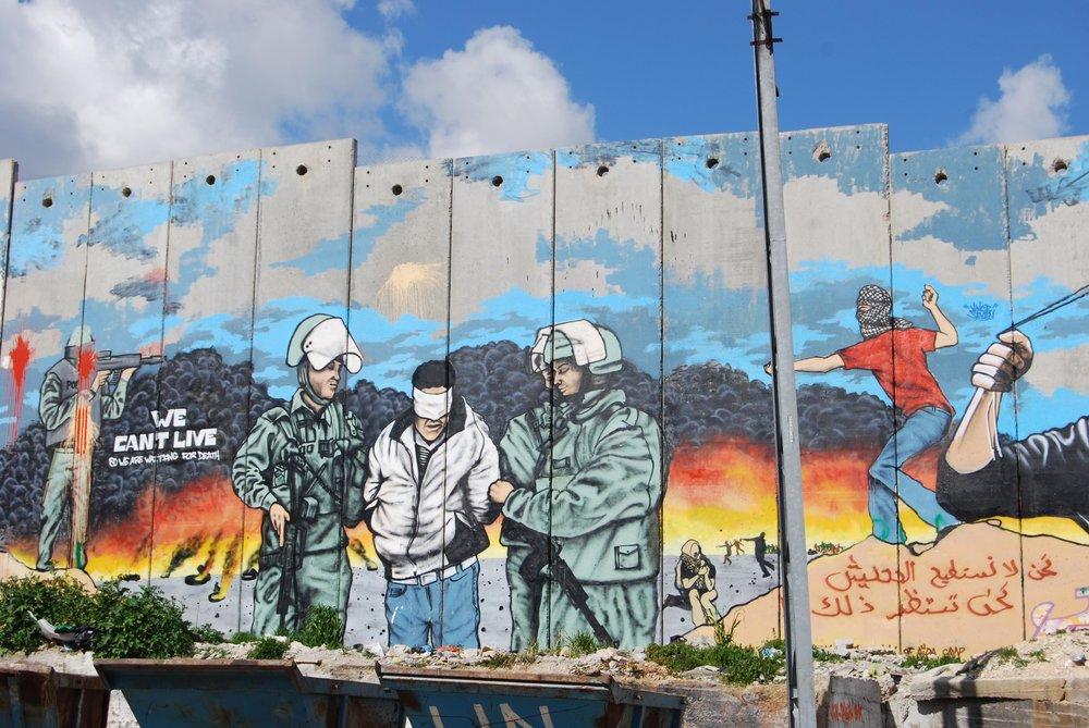 DOBBELSTRAFF: Graffitien på muren beskriver tydelig hvordan flyktningene opplever okkupasjonen. I tillegg til å bli frastjålet sitt land, blir de utsatt for folkerettsstridige overgrep på Vestbredden.