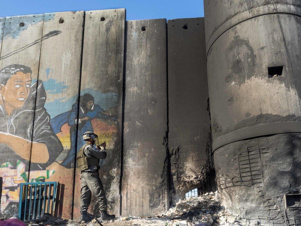 RIVER MUREN: De unge palestinerne brente bildekk for å slå sprekker i muren som går gjennom leiren. Aksjonen førte til flere ukers beleiring av israelske militære styrker. (Foto: Dan Cohen, Mondoweiss)