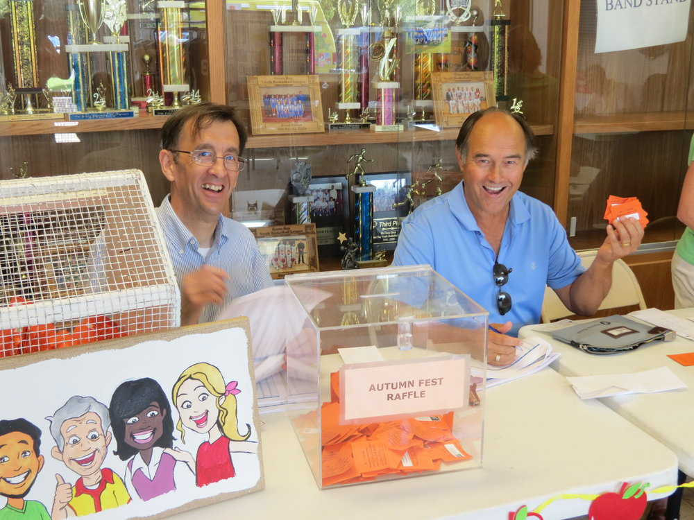 Paul Defnet (parish Trustee Treasurer) and Mike Schumacher (member) staff the Autumnfest raffle table. Autumnfest is a long-time parish community event that happens each year at the beginning of Fall.