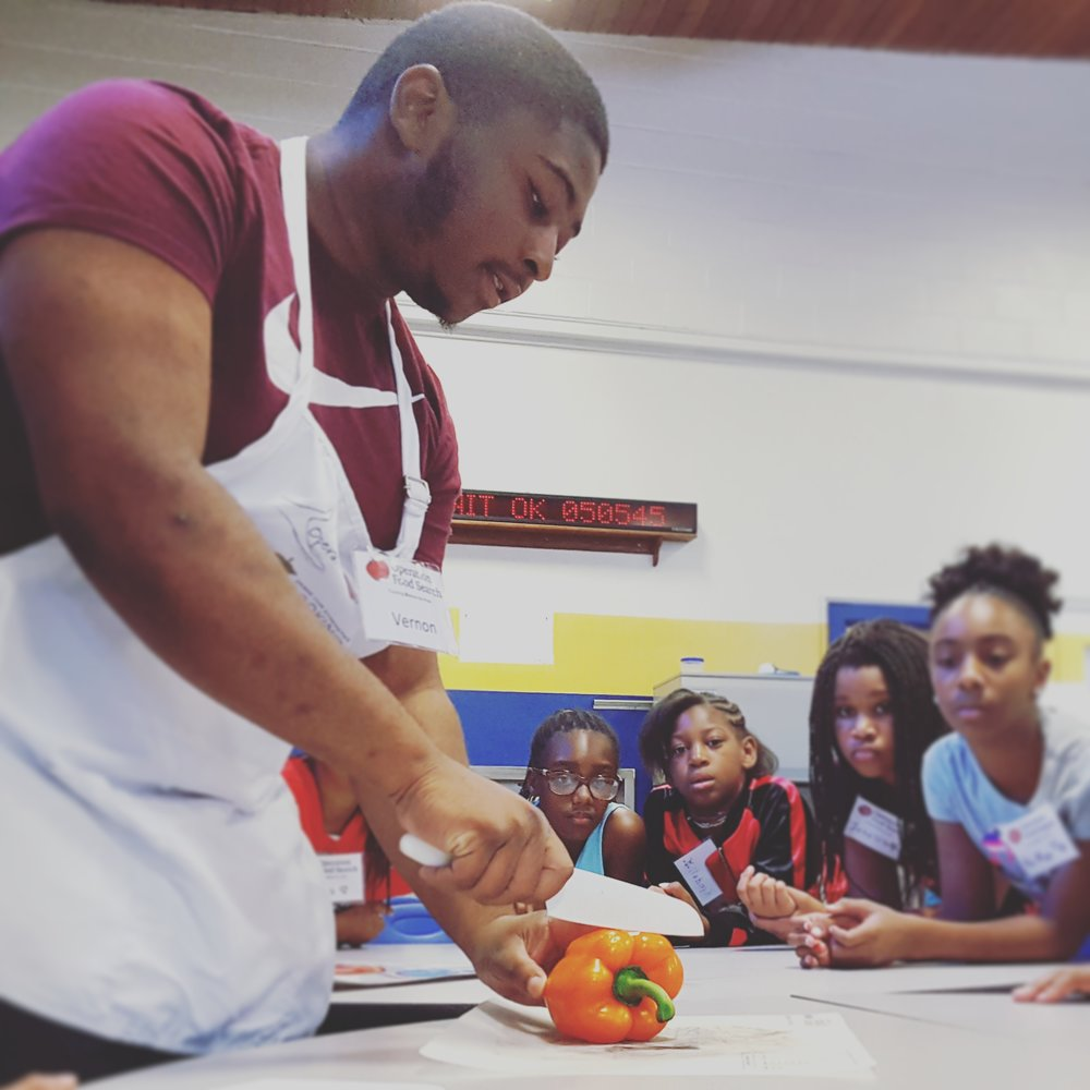 Vernon chopping vegetables as he teaches a cooking demonstration with Operation Food Search