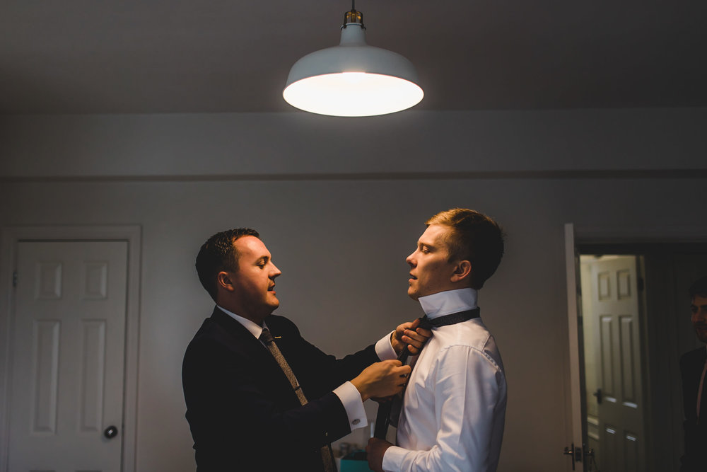 best man adjusts grooms tie