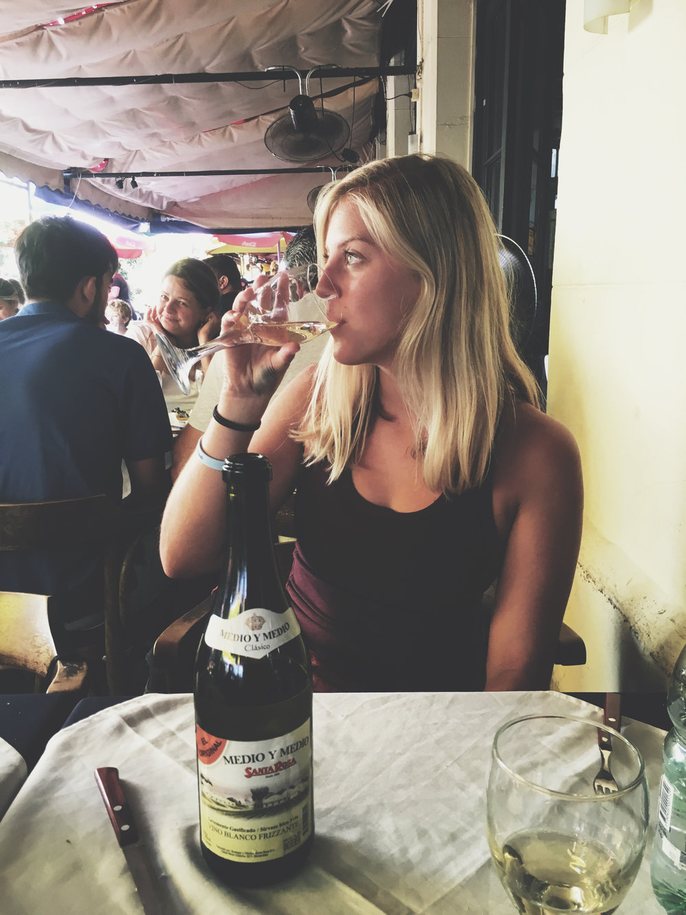 At Mercado del Puerto in Montevideo, drinking Medio y Medio and eating Parilla
