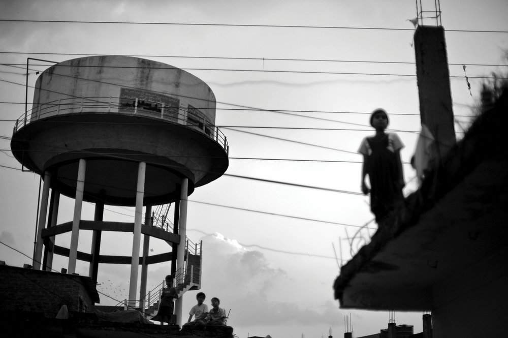 Children play on roofs near a water tower in the city of Bhopal in the state Madhya Pradesh, India.  Twenty-five years after a gas leak in the Union Carbide factory in Bhopal killed at least eight thousand people, toxic material from the 'biggest industrial disaster in history' continues to affect Bhopalis. A new generation is growing up sick, disabled and struggling for justice.