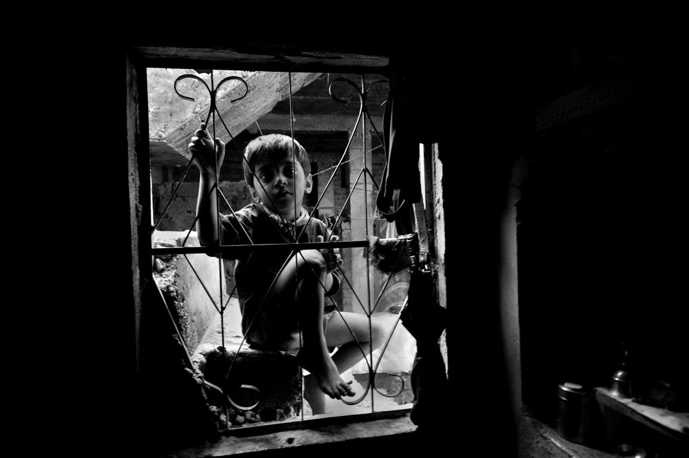A boy looks into the window of a home near the site of the Union Carbide plant behind him in the city of Bhopal in the state Madhya Pradesh, India.