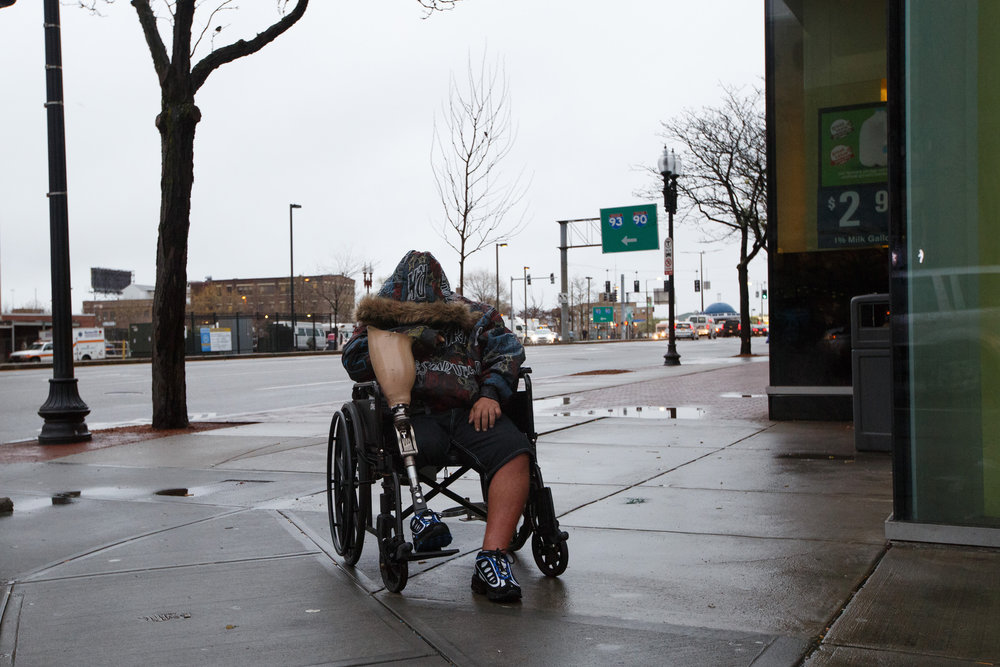 "A homeless man holds his prosthetic leg in his wheel chair in front of a Cumberland Farms. Despite an occasional sense of community on ""The Mile"",  there is little trust between addicts who often find them selves clutching on to what little they have to prevent it from being taken from them."