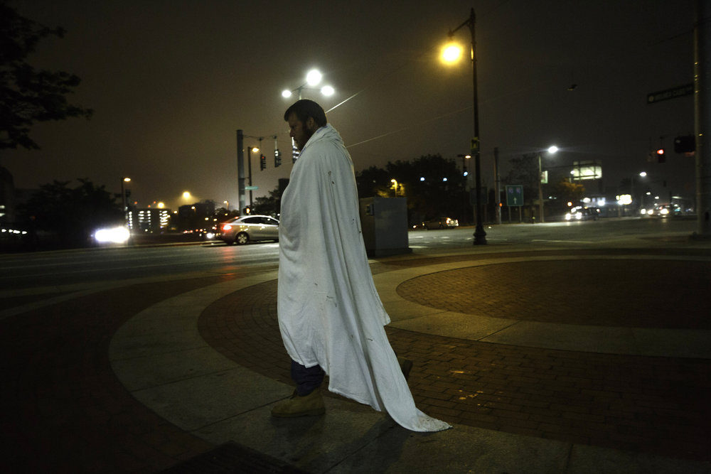 "Kenny Robertson, who has been homeless off and on for years, walks wrapped in a blanket to stave off the chill on ""Methadone Mile."" Many hover just above a slumber. White sheets draped across their shoulders, they shuffle under the streetlights like ghosts."