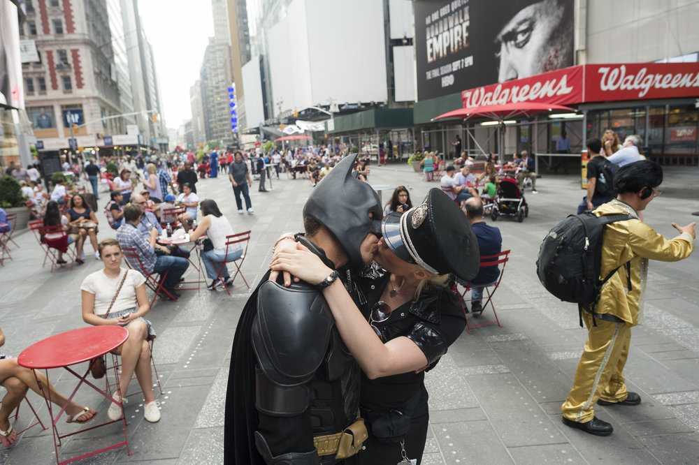 Jose kisses his girlfriend and fellow performer Elizabeth Holland during his shift as Batman in Times Square. The couple met when Martinez, dressed as Batman,  startled Holland when she walked by him six months ago. After a successful first date, he convinced her to join him in the profession.