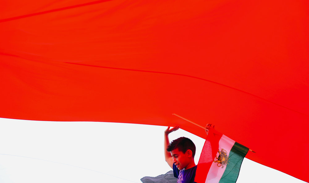 A boy walks under the flag of Iran used before the Islamic Revolution during the Persian Day Parade to celebrate the Iranian calendar New Year in New York.