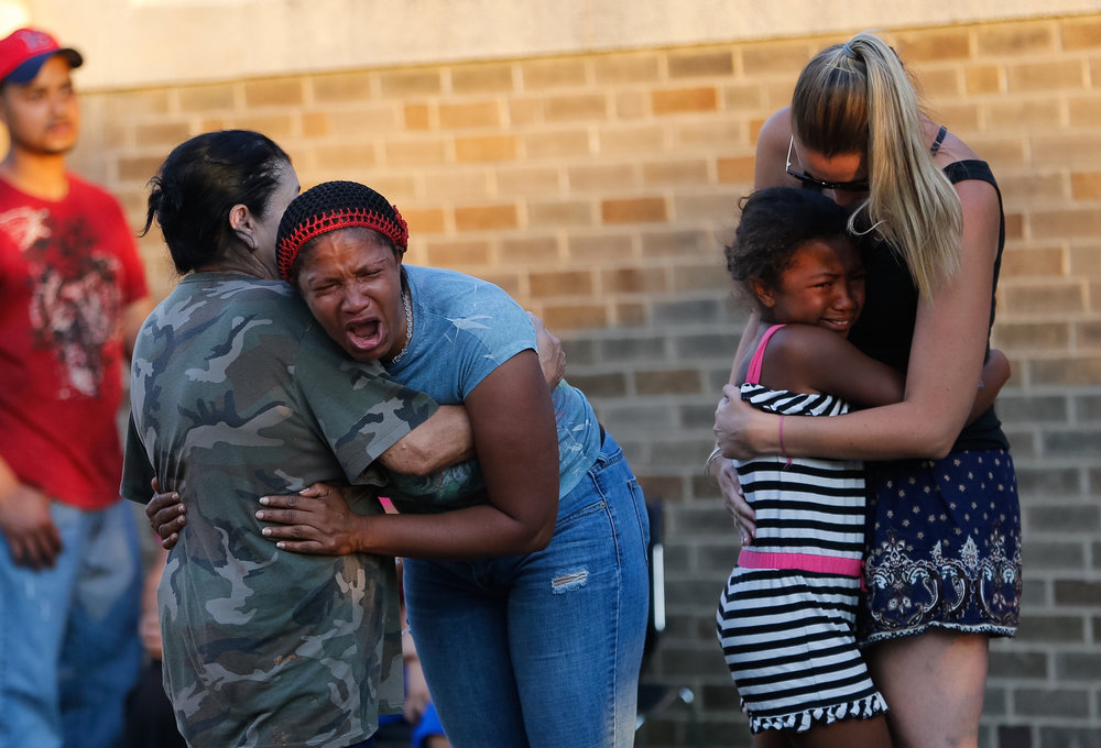 Family and friends of Kyzr Willis, a 7-year-old boy who went missing, comfort one another after finding out the boy had drowned near a command center set up to search for him at Carson Beach in Boston, MA, July 26, 2016.