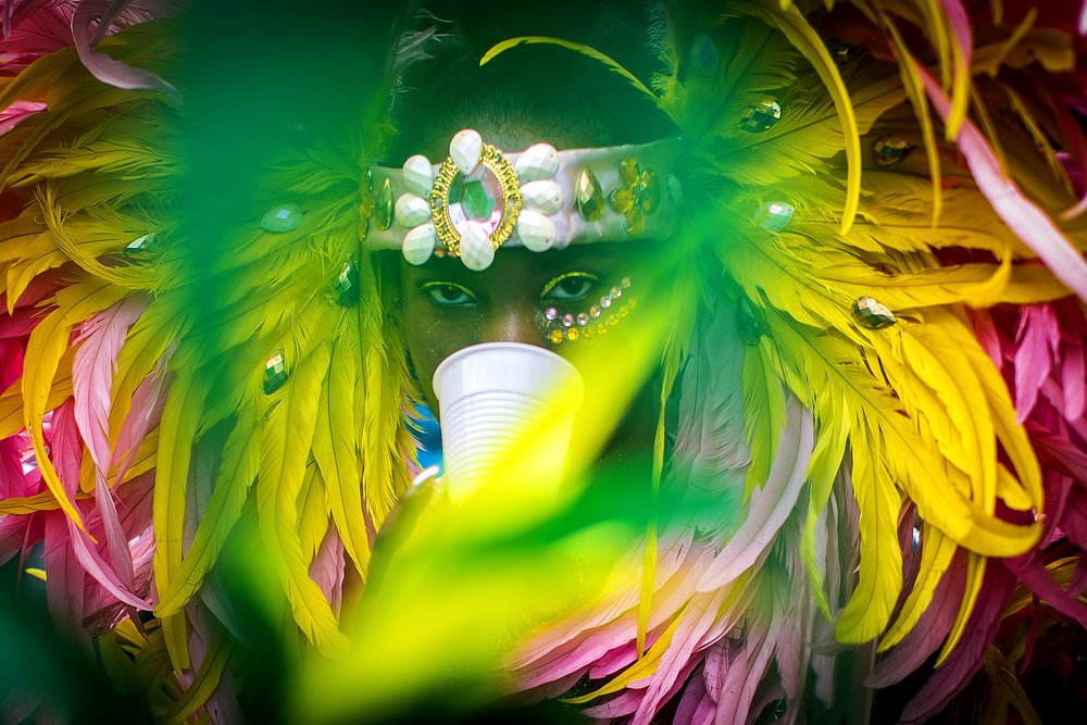 A woman carries a cup in her teeth as she marches in the Cambridge Carnival Parade in Cambridge, MA, September 11, 2016.