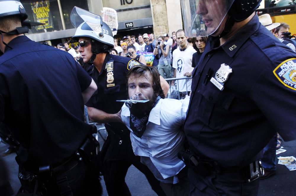 Law enforcement officers arrest demonstrators after a papier-mâché dragon was set on fire by anarchists on Seventh Avenue near Madison Square Garden August 29, 2004, in New York City. Police arrested dozens as thousands of protesters marched to the site of the Republican National Convention.
