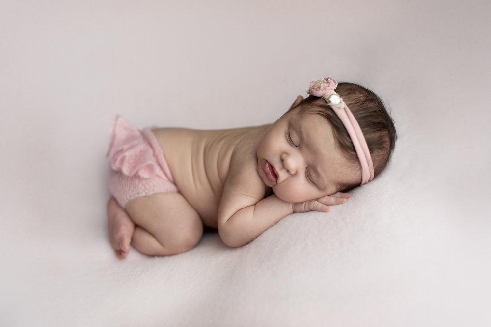 Pink ruffle butt shorts on a sleeping newborn baby girl