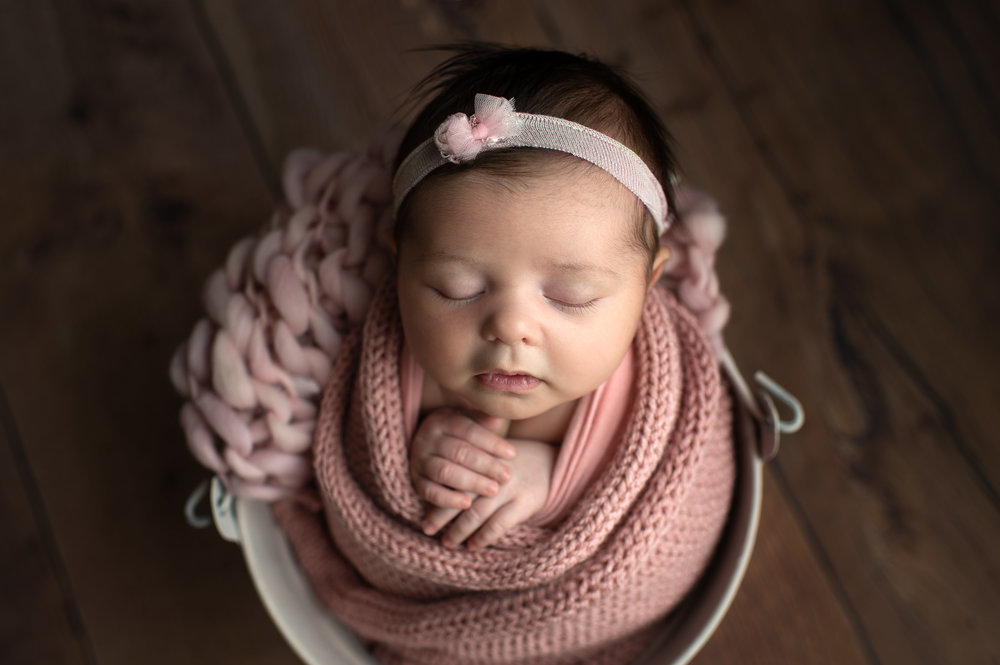 Sleeping newborn girl in a bucket wrapped in pink