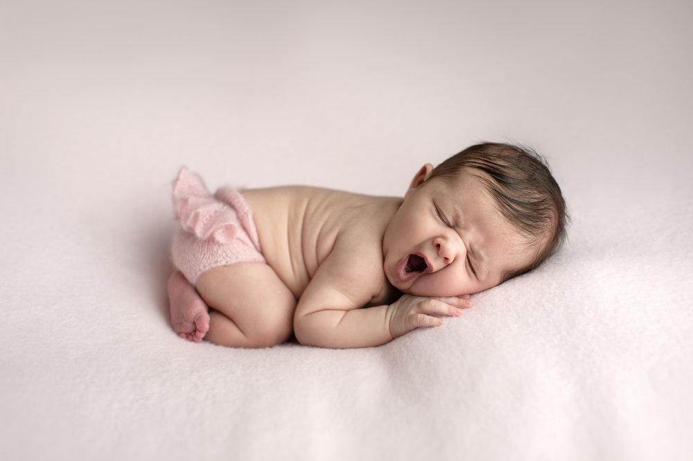 Yawning newborn girl on a pink blanket