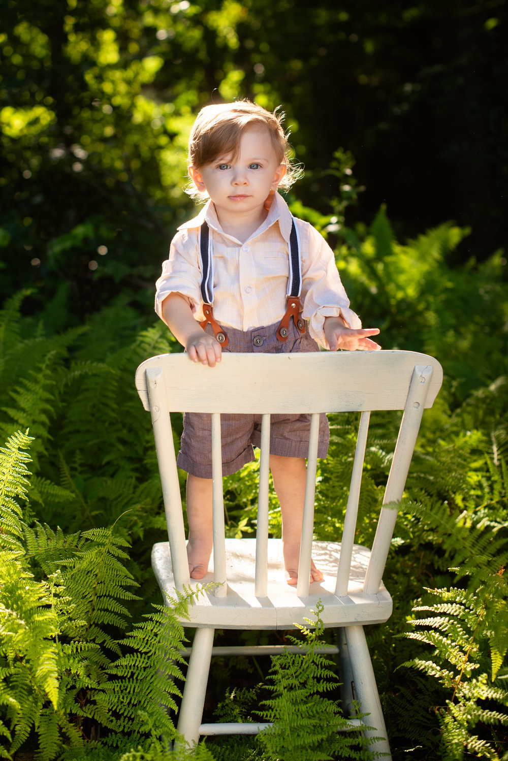 one year old boy standing on a chair in the ferns in connecticut photo session