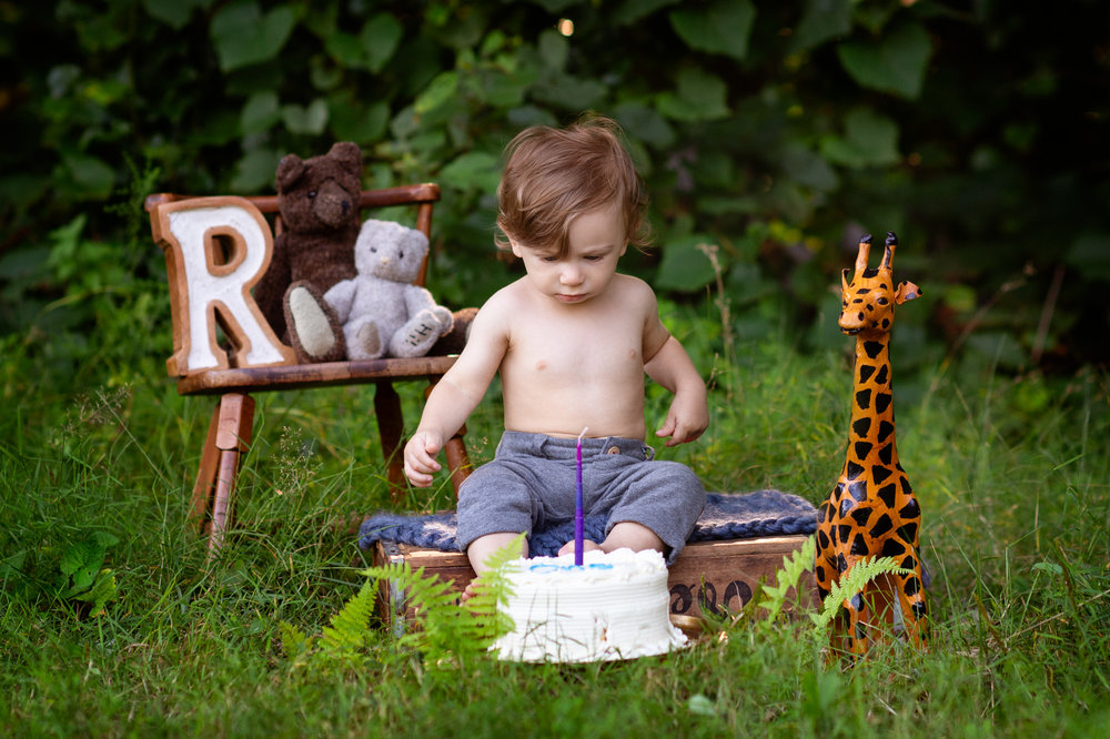 1 year old boy at an outdoor cake smash looking hesitant