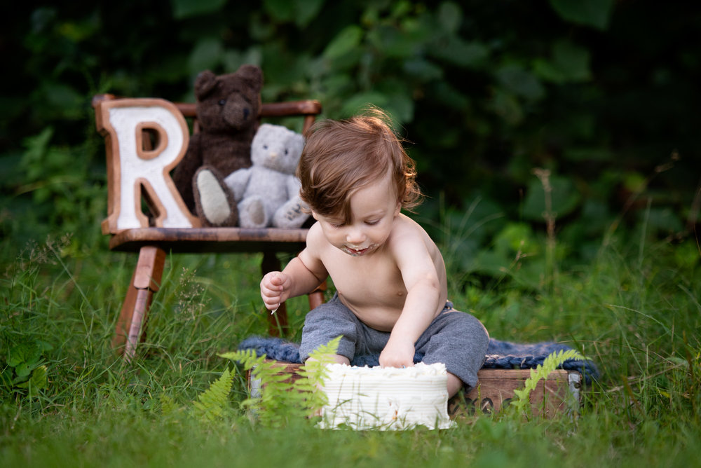 one year old boy diving into his cake at his outdoor ct cake smash session