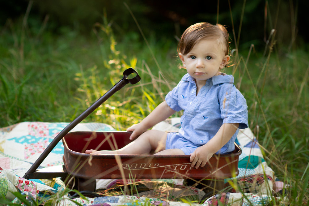 one year old boy in a radio flyer red wag on an antique quilt