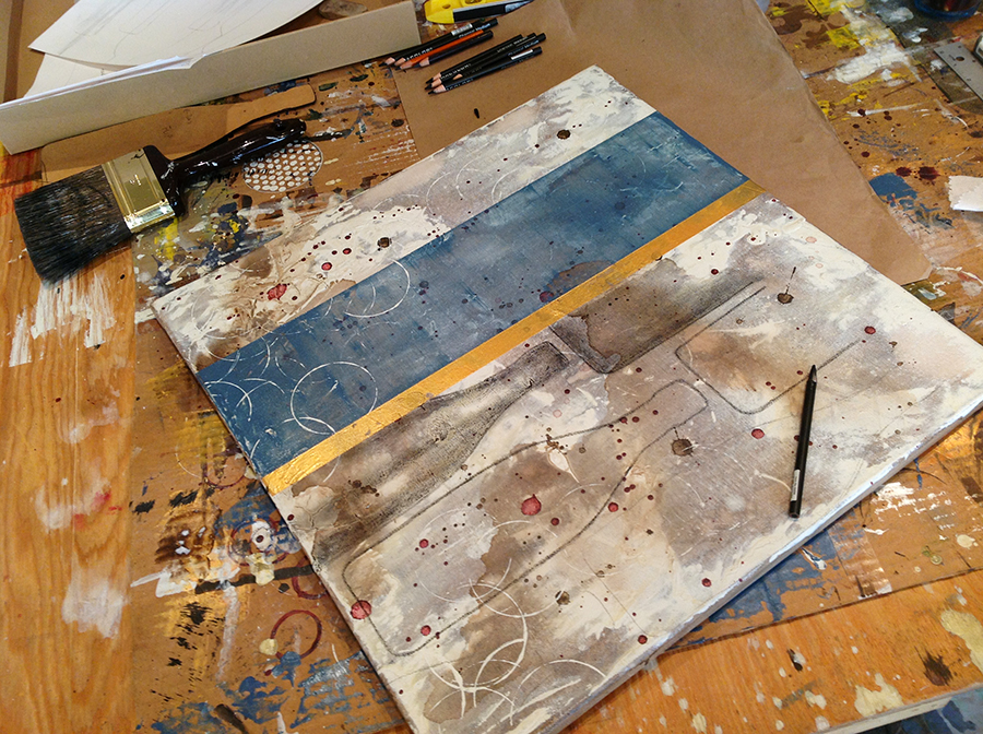 Wine bottles and abstract layers of blue brown and gold in a progressing painting in the studio of artist Taylor Smith