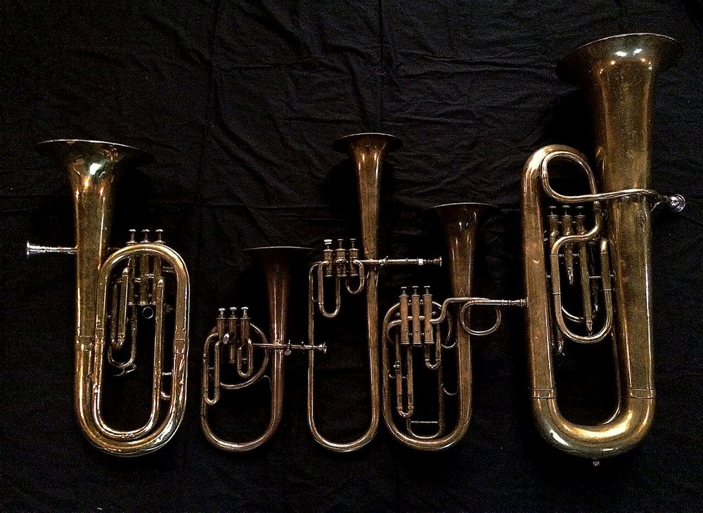 Left to Right: Baritone saxhorn in B-flat by Couesnon (44139, 94 Rue D'angouleme Exposition Universelle De Paris, 1900), Contralto saxhorn in B-flat by J. Grass (32 Rue des Ponts de Comines, Lille, est. 1868, Contralto saxhorn in B-flat by Adolphe Sax (Paris, c. 1849-1850), sold by Distin & Sons, Cranbourne St. Leicester Square, London, Tenor saxhorn in F/E flat/D by Antoine Courtois (Paris, c. 1855), sold by Arthur Chappell (London), Contrabass saxhorn in E-flat by E. Daniel (7167, Marseille, c. 1850).