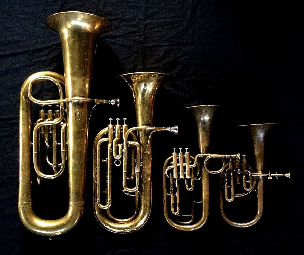 Left to Right: Contrabass saxhorn in E-flat by E. Daniel (7167, Marseille, c. 1850), Baritone saxhorn in B-flat by Couesnon (44139, 94 Rue D'angouleme Exposition Universelle De Paris, 1900), Tenor saxhorn in F/E flat/D by Antoine Courtois (Paris, c. 1855), sold by Arthur Chappell (London), Contralto saxhorn in B-flat by J. Grass (32 Rue des Ponts de Comines, Lille, est. 1868.