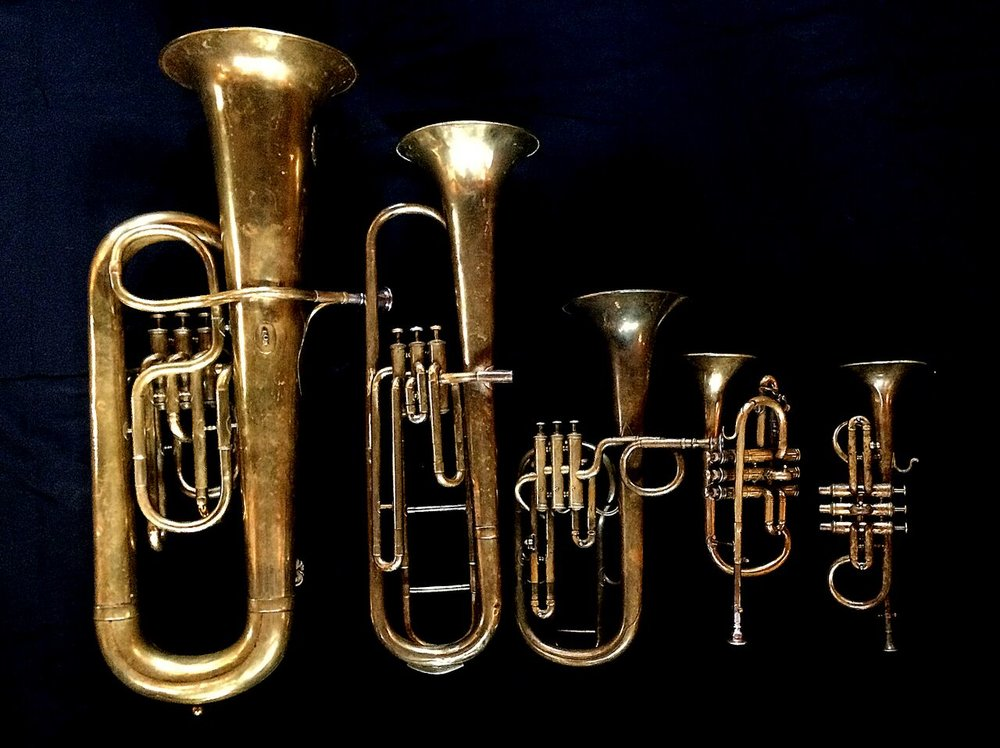 Left to Right: Contrabass saxhorn in E-flat by E. Daniel (7167, Marseille, c. 1850), Baritone saxhorn in C/B flat by Couturier (Lyon, c. 1865), Tenor saxhorn in F/E flat/D by Antoine Courtois (Paris, c. 1855), sold by Arthur Chappell (London), Cornet in E-flat by Couesnon (94 Rue D'angouleme Exposition Universelle De Paris 1900), Cornet in E-flat by  Henry Distin (Gt. Newport Street, London, c. 1851-1868),.