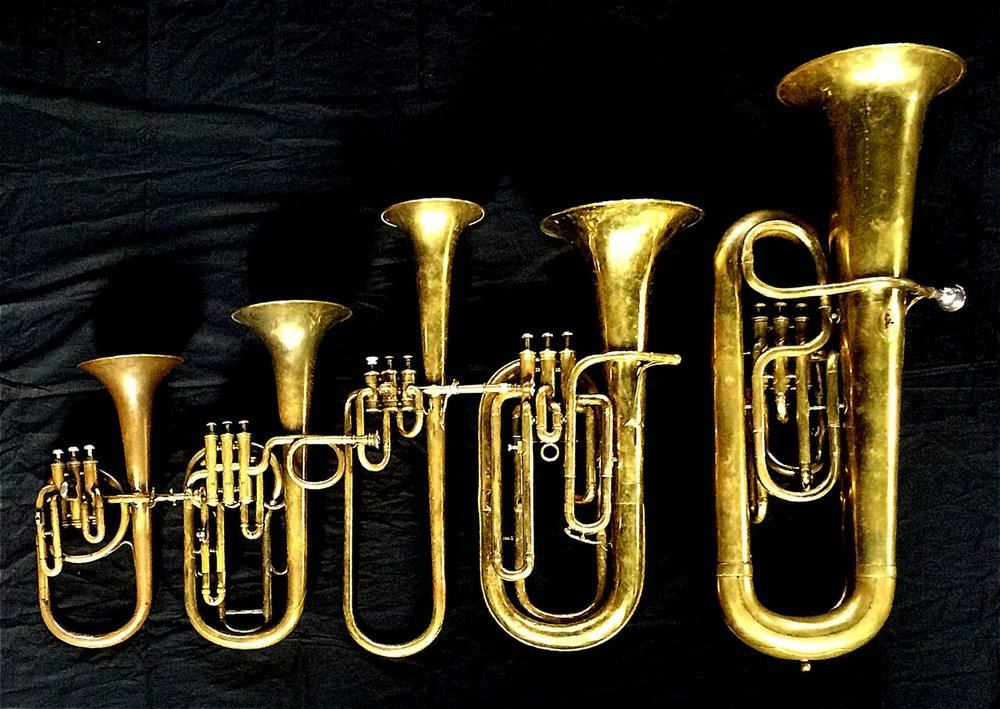 Left to Right: Contralto saxhorn in B-flat by J. Grass (32 Rue des Ponts de Comines, Lille, est. 1868, Tenor saxhorn in F/E flat/D by Antoine Courtois (Paris, c. 1855), sold by Arthur Chappell (London), Contralto saxhorn in B-flat by Adolphe Sax (Paris, c. 1849-1850), sold by Distin & Sons, Cranbourne St. Leicester Square, London, Baritone saxhorn in B-flat by Couesnon (44139, 94 Rue D'angouleme Exposition Universelle De Paris, 1900), Contrabass saxhorn in E-flat by E. Daniel (7167, Marseille, c. 1850).