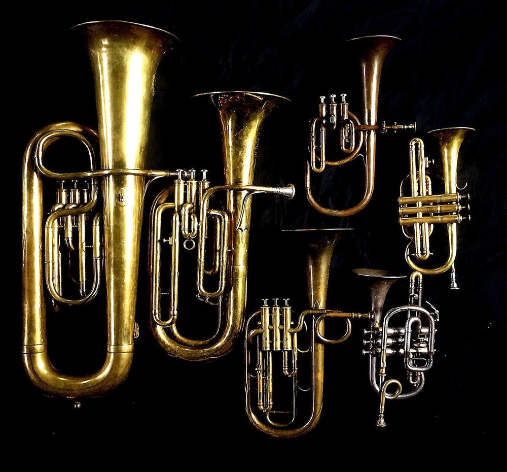Left to Right: Contrabass saxhorn in E-flat by E. Daniel (7167, Marseille, c. 1850), Baritone saxhorn in B-flat by Couesnon (44139, 94 Rue D'angouleme Exposition Universelle De Paris, 1900), Tenor saxhorn in F/E flat/D by Antoine Courtois (Paris, c. 1855), sold by Arthur Chappell (London),  Contralto saxhorn in B-flat by J. Grass (32 Rue des Ponts de Comines, Lille, est. 1868., Cornet in C/B-flat by Henry Distin New American Model (9580, Williamsport, PA, c. 1895), Cornet in B-flat/A by F. Besson (44292, 96 Rue D'angouleme, Paris c. 1892).