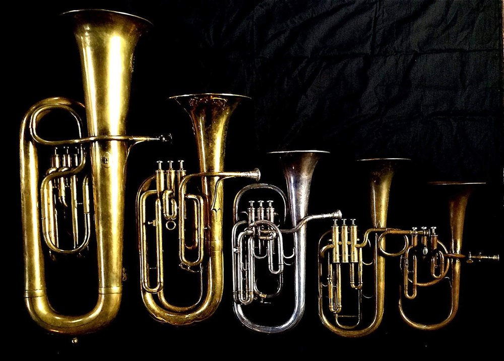 Left to Right: Contrabass saxhorn in E-flat by E. Daniel (7167, Marseille, c. 1850), Baritone saxhorn in B-flat by Couesnon (44139, 94 Rue D'angouleme Exposition Universelle De Paris, 1900), Tenor saxhorn in E flat by Boosey & Co (47317, 295 Regent Street, London, 1900). Tenor saxhorn in F/E flat/D by Antoine Courtois (Paris, c. 1855), sold by Arthur Chappell (London),  Contralto saxhorn in B-flat by J. Grass (32 Rue des Ponts de Comines, Lille, est. 1868.
