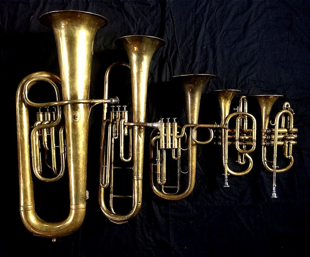 Left to Right: Contrabass saxhorn in E-flat by E. Daniel (7167, Marseille, c. 1850), Baritone saxhorn in C/B flat by Couturier (Lyon, c. 1865), Tenor saxhorn in F/E flat/D by Antoine Courtois (Paris, c. 1855), sold by Arthur Chappell (London), Cornet in B-flat/A by F. Besson (44292, 96 Rue D'angouleme, Paris c. 1892), Cornet in E-flat by Couesnon (94 Rue D'angouleme Exposition Universelle De Paris 1900).