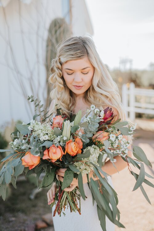 southern_wedding_flowers_botanicals_bouqet_bride_looking_at_flowers_wedding_dau_knoxville_asheville_rustic_wild_romantic