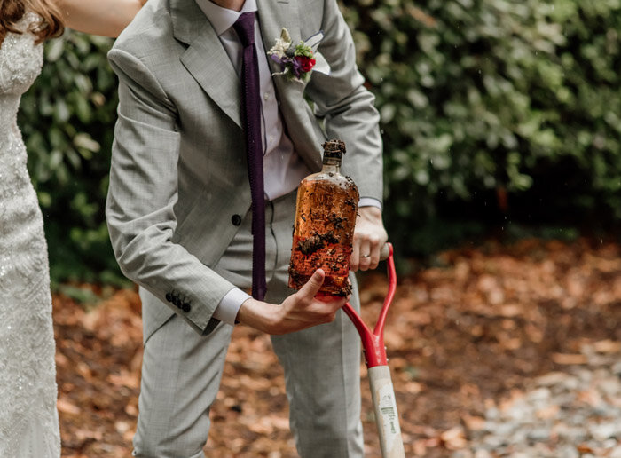 burry_the_bourbon_southern_wedding_tradition_for_good_weather_groom_holding_bourbon_look_for_the_light_photo_video