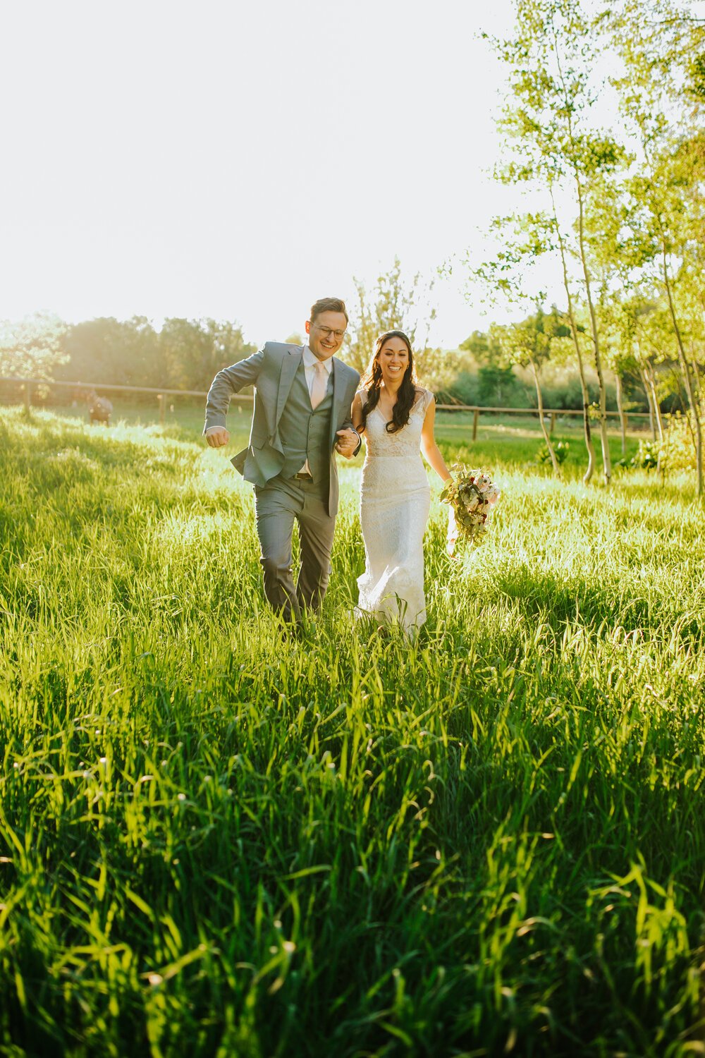 summer_wedding_outdoors_southern_traditions_joyful_knoxville_bride_couple_walking_grass_field_holding_hands_tennessee_photographer_look_for_the_light_photo_video