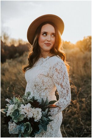 fall-bride-looking-behind-shoulder-while-wearing-sun-hat-sun-setting-bridals-look-for-the-light-photo-video