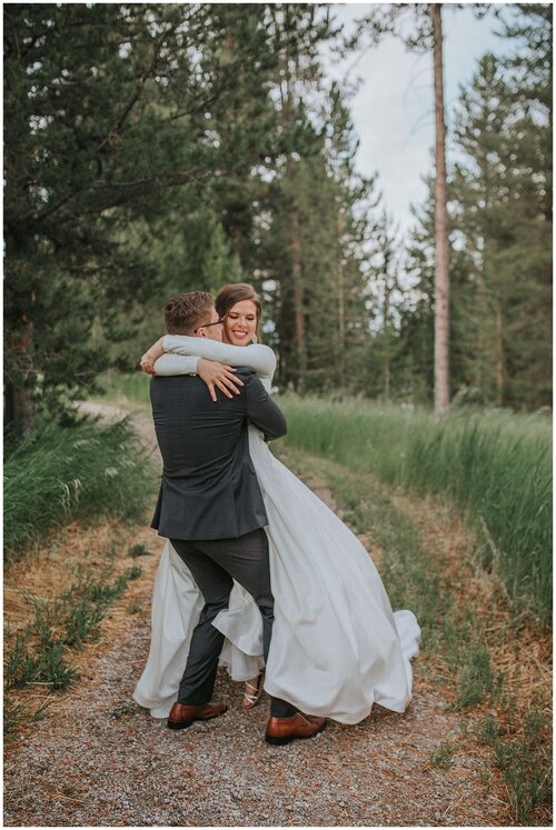couple-hugging-while-on-a-trail-big-wedding-dress-mountains-greenery-elopement-session