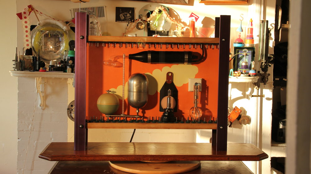 "Cornell Killer, 2011.   (ionized air electric-transfusion* shadowbox lamp)   *employs Nicola Tesla's free electricity air-transmittance concept.    Includes: Piano pegboards, a Violet Ray, ""Maggott"" in acrylic paint, glass Baumanometer tube, Stainless steel Welch's grape juice factory Juice-Vat gauge float, bakelite telephone parts, a friend's silver-encased molar, micro flourescent lamp tubes, and the electron gun from a  ociloscope picture tube."