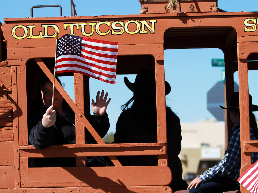 A person riding in the Arizona/Sonora Western Heritage Foundation at Old Tucson carriage waves and flies an American flag during the Tucson Rodeo Parade Feb. 23, 2017.