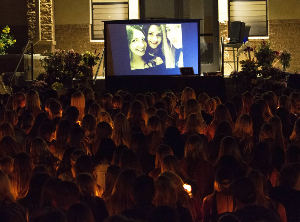 The UA community watches a slideshow made by close friends of Christiana Duarte, who was killed in the Las Vegas shooting, at her memorial service hosted by the Arizona Zeta Omicron chapter of Sigma Kappa sorority at Greek Heritage Park, Oct. 10, 2017. It's estimated more than 500 people attended the service as the sorority ran out of candles to hand out.