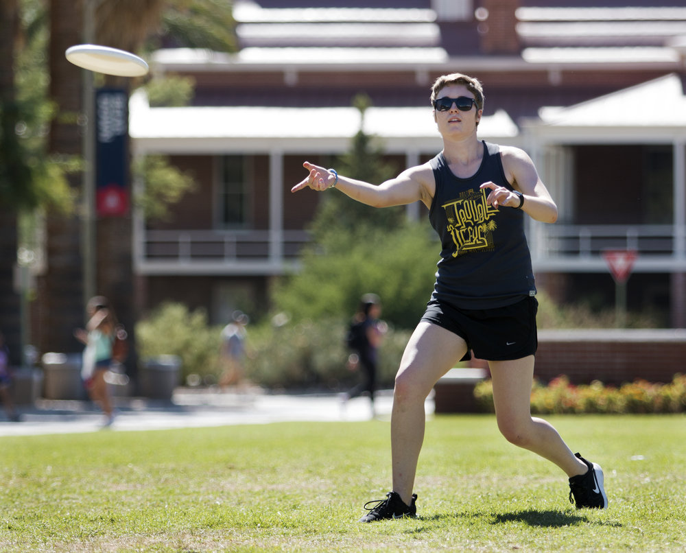 Caroline Schulte, a junior studying biomedical engineering and a member of the women's ultimate frisbee club team, practices with her teammates on the University of Arizona Mall Aug. 21, 2017.