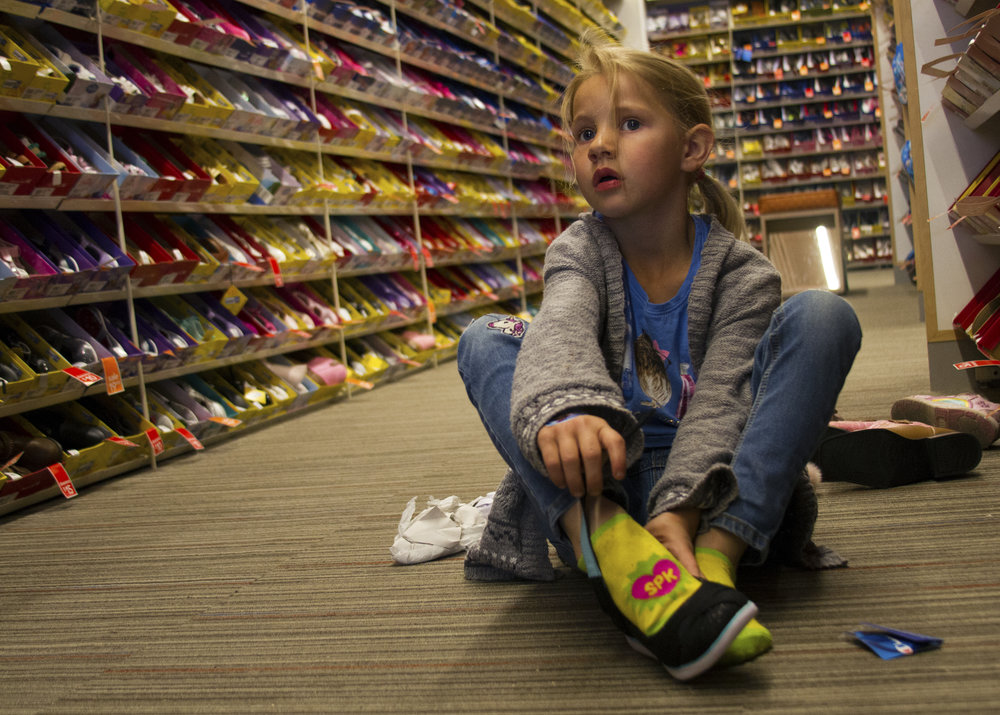 Kindergartener Sarah Swafford, 5, from Tucson, Ariz. eyes a pair of pink cowgirl boots while trying on a pair of flats at at the Payless Super Store on Broadway March 9, 2017.