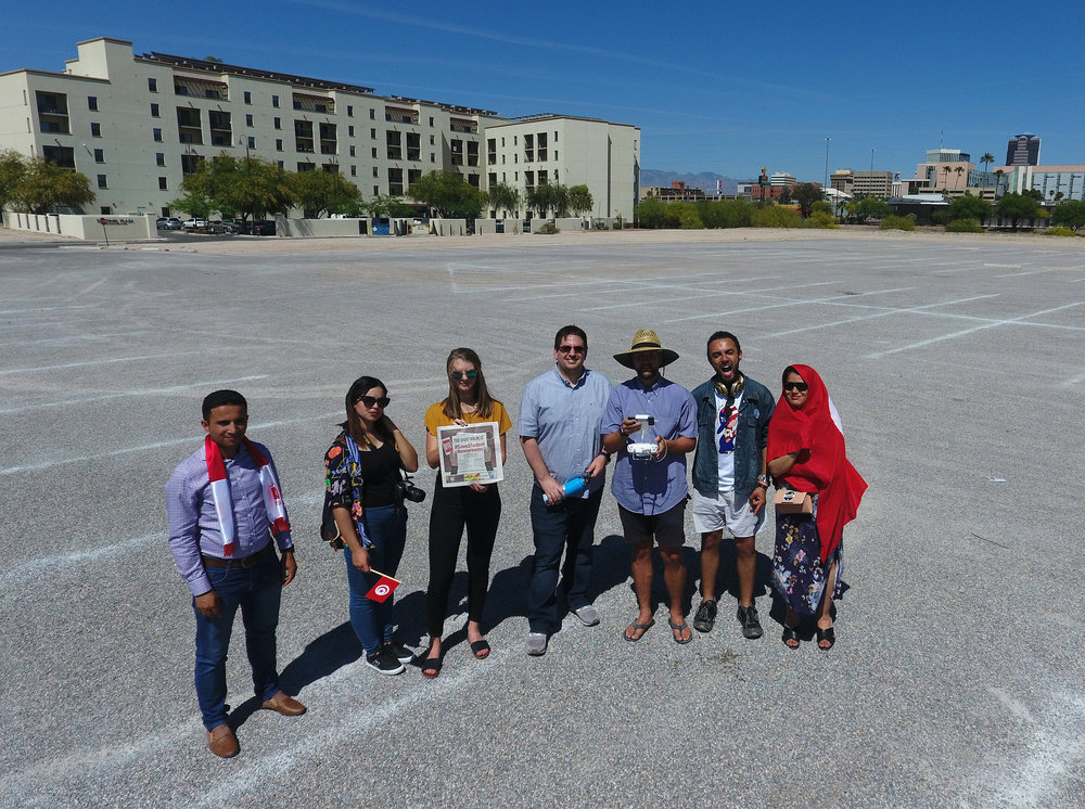 I, third from the left, hold up The Daily Wildcat's #SaveStudentNewsrooms April 18, 2018 edition. This photo was taken with a drone during a mobile journalism workshop, part of the Al Jisr Exchange media program with the University of Arizona School of Journalism and students from Tunisia.
