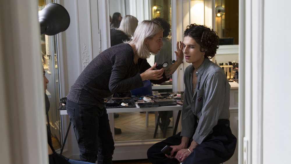 "Parisian model Thomas Jullien gets his makeup done before modeling in The Classics Paris' Autumn/Fall 2018-2019 Presentation March 7, 2018 at the former residence of Gabrielle ""Coco"" Chanel in Paris, France."