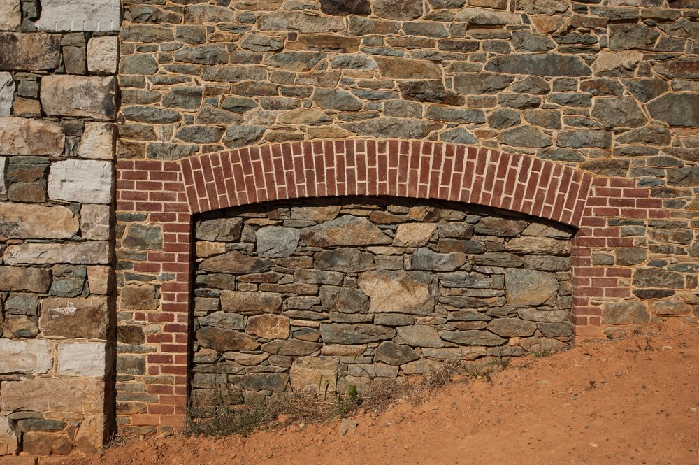 Brick arches suggest past repairs on a historic barn.