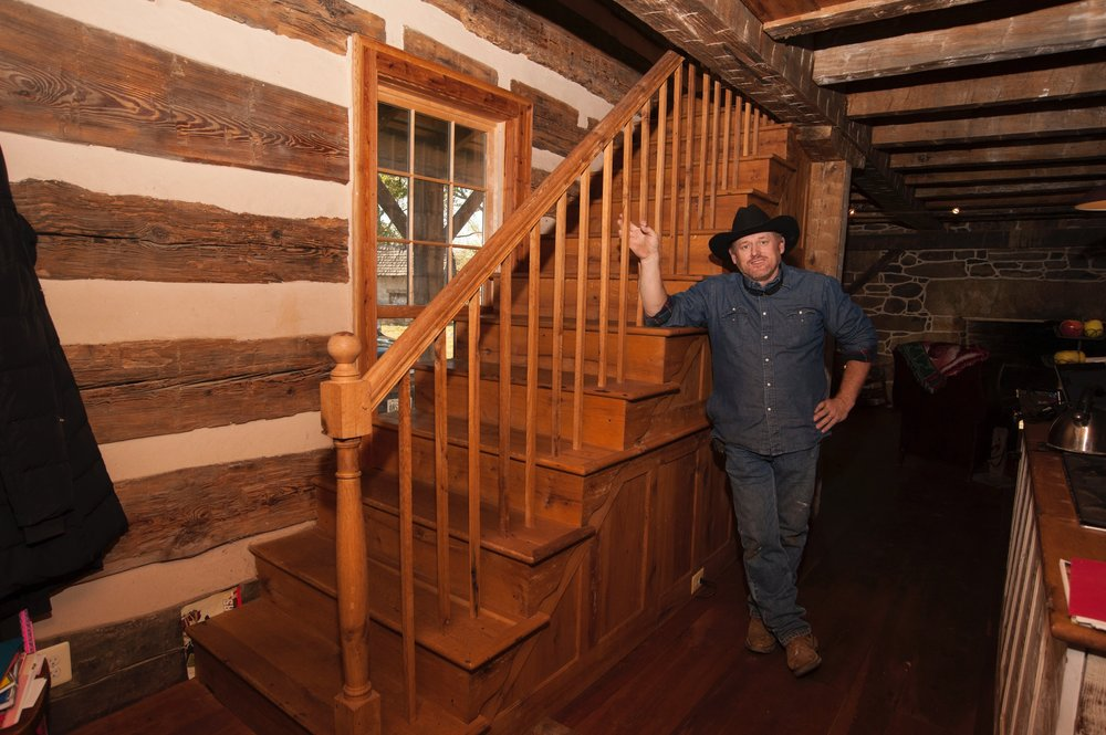 Allen Cochran stands next to the original newel post of the log building.