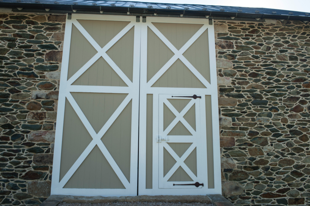 Barn doors incorporate smaller entry door.