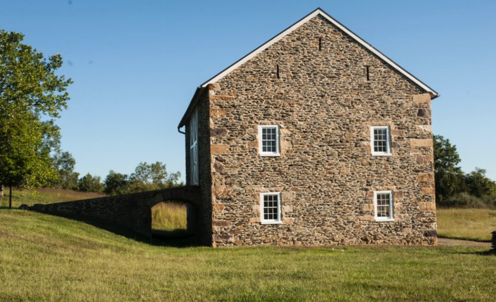 Period inspired barn features new windows set into custom frames of salvaged materials.