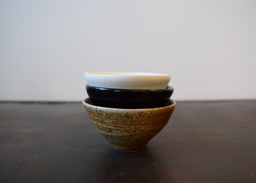 Each set contains a woodfired bowl, showing off the raw clay, as well as a white and black glazed bowl.